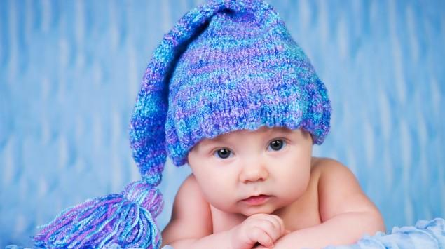 Baby mit Pudelmütze schaut in die Kamera.