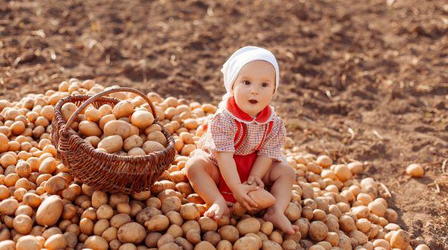 Ein Baby sitzt auf einem Berg Kartoffeln.