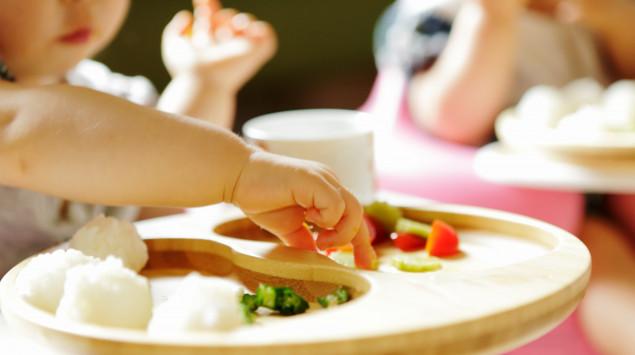 Ein Baby isst auf einem Hochstuhl Finger Food