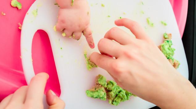 Man sieht eine Erwachsenen- und eine Babyhand mit Brothäppchen mit Avocado