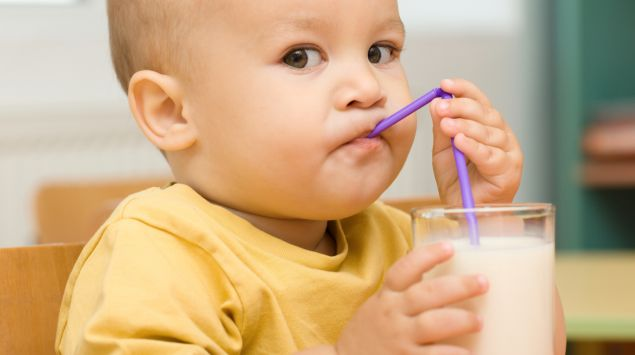 Ein Baby trinkt Milch aus einem Glas.