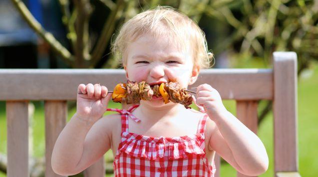 Ein kleines Kind isst einen Fleisch-Gemüse-Spieß.