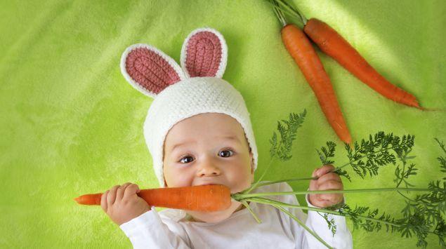 Ein Baby im Hasenkostüm knabbert an Möhren.