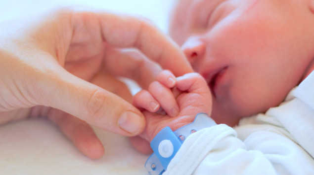 Man sieht ein neugeborenes Baby.