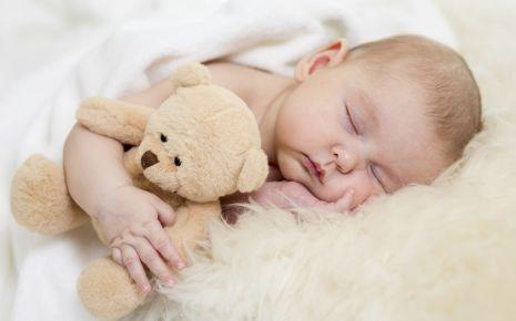 Ein Baby schläft, im Arm hält es einen Teddy