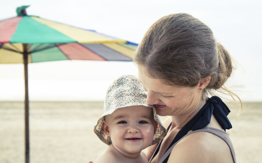 Eine Mutter hält am Strand ihr Baby auf dem Arm, das einen Sonnenhut auf hat.