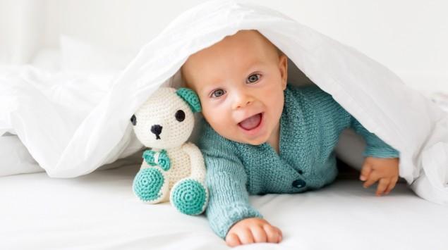Ein lachendes Baby schaut unter einer Decke hervor.