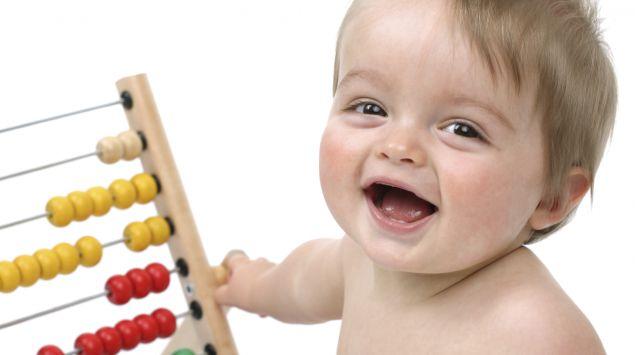 Ein lachendes Baby spielt mit einem Abakus.