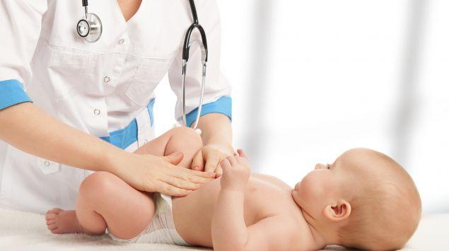 Eine Ärztin tastet den Bauch eines Babys ab.