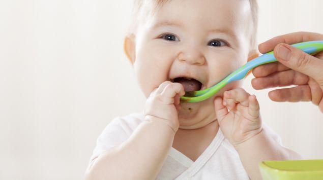 Jemand füttert ein Baby mit Brei.