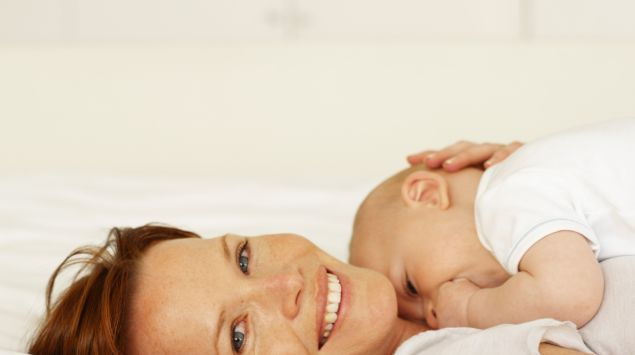 Das Bild zeigt eine Mutter, die ihr neugeborenes Baby im Arm hält.