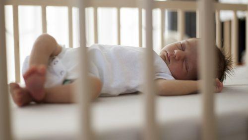Ein Baby liegt schlafend in einem Gitterbett.