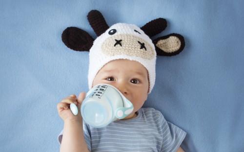 Ein Baby mit einer Kuhmütze trinkt aus einem Becher Milch.
