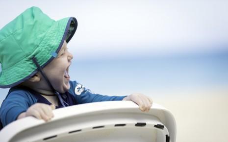 Ein Baby mit Sonnenhut und langärmeligem Oberteil klammert sich lachend an einen Kindersitz am Strand.