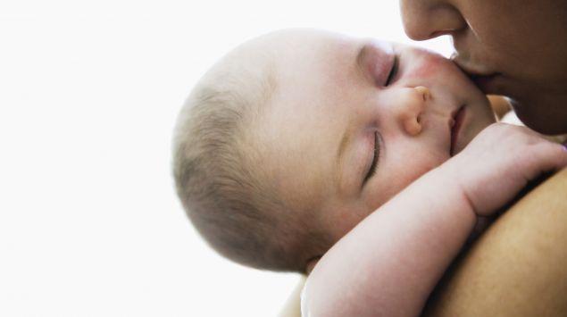 Schlafendes Baby auf dem Arm der Mutter
