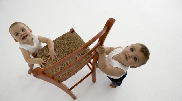 Zwei Babys stehen an einem Stuhl.