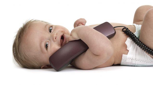 Ein Baby liegt auf dem Rücken und hält einen Telefonhörer im Arm.