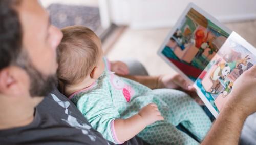 Das Bild zeigt einen Vater, der mit seinem Baby ein Bilderbuch ansieht.