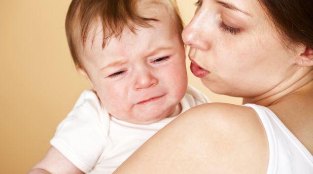 Eine Frau hält ein weinendes Baby im Arm.