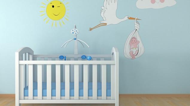 Baby-Gitterbett vor einer bunten Wand.