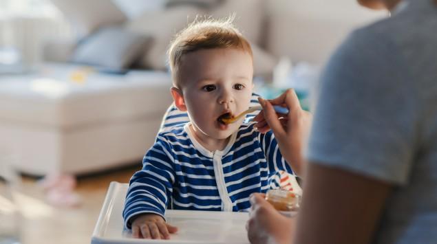 Das Bild zeigt einen kleinen Jungen, der von seiner Mutter mit Babybrei gefüttert wird.