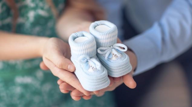 Ein Mann und eine Frau halten ein Paar blaue Babyschuhe in den Händen.