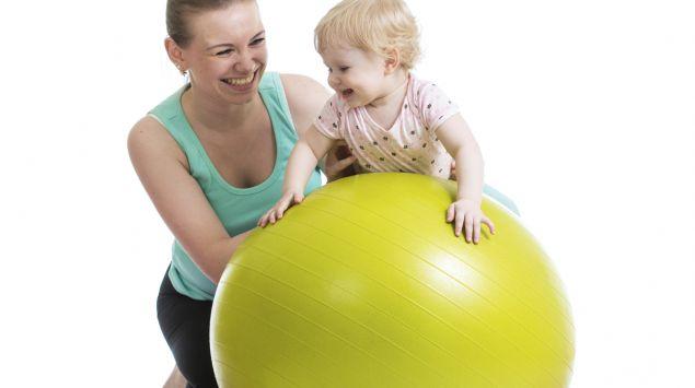 Mutter balanciert Kleinkind auf Gymnastikball.