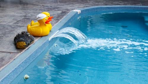 Zwei gelbe Badeenten am Rand eines Schwimmbads