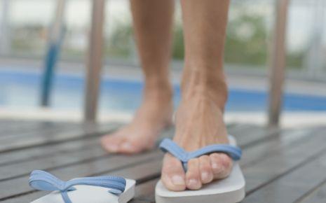 Dornwarzen: Eine Frau schlüpft in Badelatschen, die am Rand des Schwimmbeckens liegen.