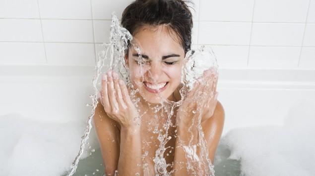 Junge Frau spritzt sich in der Badewanner Wasser ins Gesicht