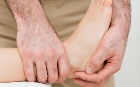 Das Bild zeigt einen Arzt, der eine Bänderdehnung mithilfe des Aufklapptests diagnostiziert.