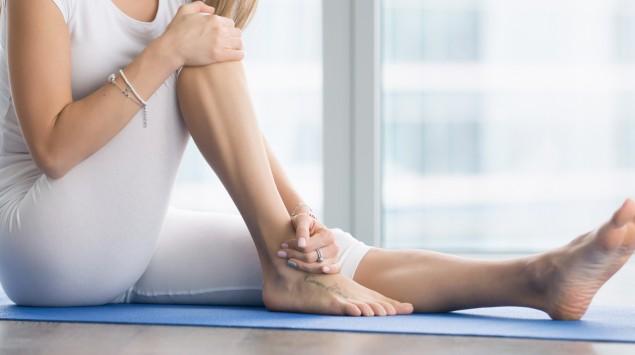 Eine Frau hält sich den schmerzenden Knöchel.