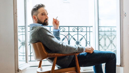 Ein bärtiger Mann sitz neben einem geöffneten Fenster und raucht eine Zigarette.