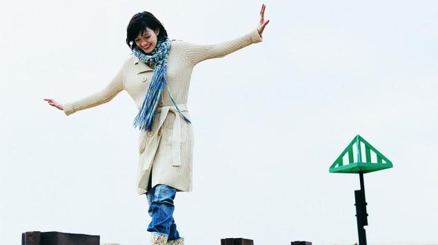 Das Bild zeigt eine Frau, die am Strand auf einem Balken balanciert.