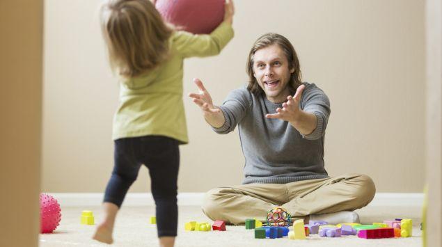 Ein Kind wirft seinem Vater einen Ball zu.