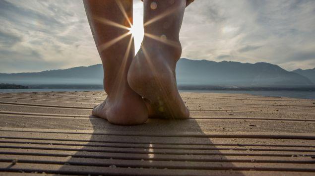 Eine Frau steht barfuß auf einem Bootssteg.