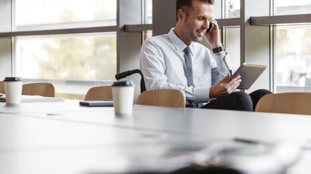 Das Bild zeigt einen Rollstuhlfahrer mit Laptop und Telefon in einem Konferenzraum.