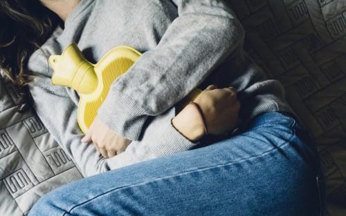 Eine Frau mit Bauchschmerzen liegt im Bett und hält sich eine Wärmflasche auf den Bauch.