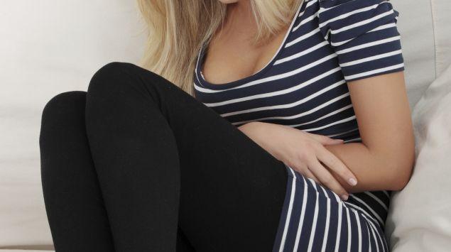 Eine Frau sitzt mit Bauchschmerzen auf dem Sofa.