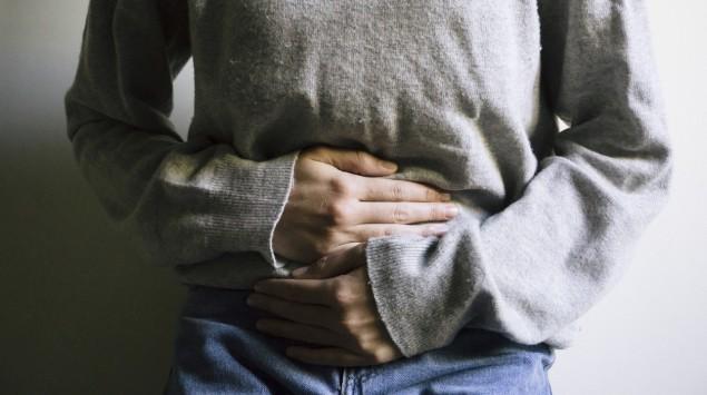 Eine Frau hält sich den Bauch.