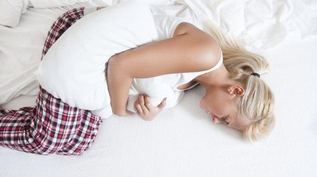 Das Bild zeigt eine junge Frau, die mit Bauchkrämpfen auf dem Bett liegt.