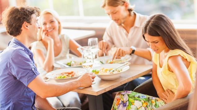 Eine Frau sitzt mit anderen Menschen beim Essen und hat Bauchschmerzen.
