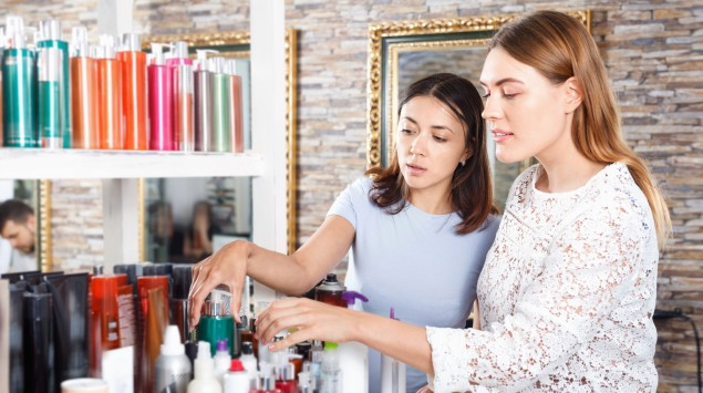 Zwei Teenager schauen sich verschiedene Beautyprodukte an.
