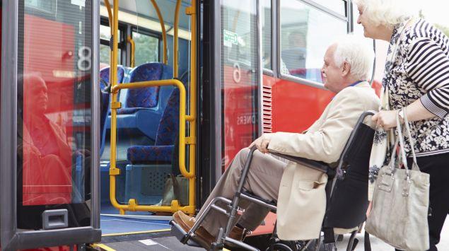 Das Bild zeigt einen Rollstuhlfahrer, der in einen Bus einsteigt.