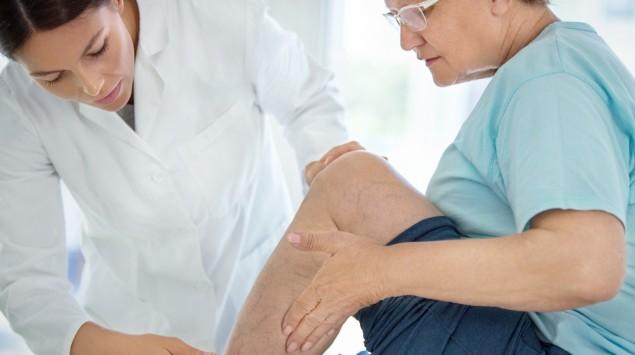 Eine Ärztin begutachtet das Bein einer Patientin.