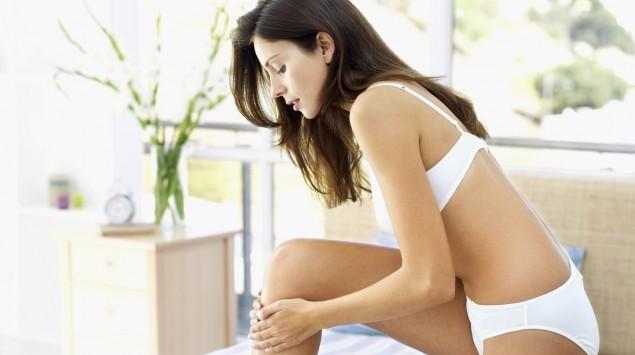 Das Bild zeigt eine Frau, die ihr rechtes Bein eincremt.