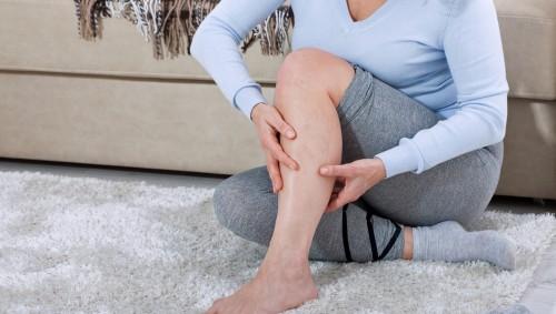 Eine Frau sitzt vor dem Sofa auf dem Boden und untersucht ihr Bein.
