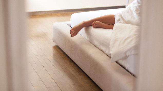 Die Beine einer Frau schauen unter der Bettdecke hervor.