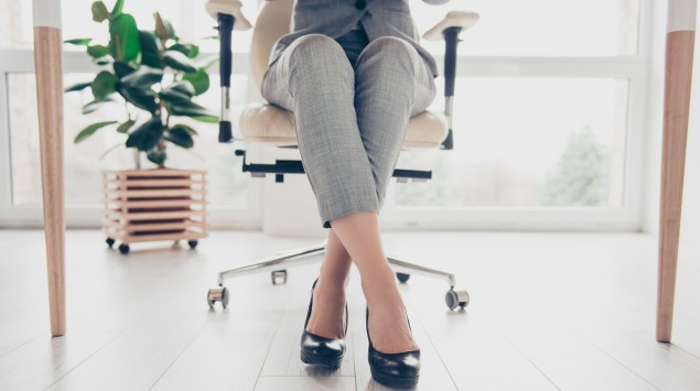 Man sieht die Beine einer Frau, die auf einem Bürostuhl sitzt.