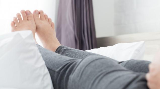 Eine schwangere Frau hat ihre Beine auf einem Bett hochgelegt.